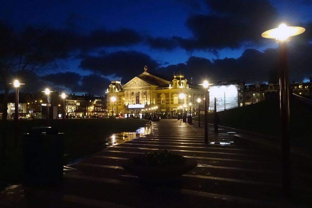 Concertgebouw bij avond met donkere wolken